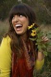 Fleurs sentantes de belle femme Photographie stock libre de droits