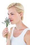 Fleurs sentantes de femme blonde magnifique photographie stock libre de droits