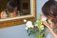 Fleurs sentantes de fille Image stock