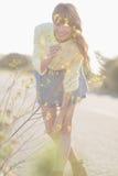 Fleurs sentantes de fille gaie de hippie Photos stock