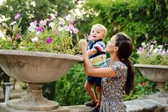 Fleurs sentantes de fils de mère et d'enfant en bas âge Photos stock