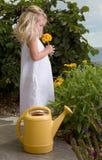 Fleurs sentantes de jeune fille Photographie stock libre de droits
