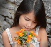 Fleurs sentantes de jeune fille Image stock