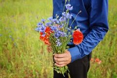 Fleurs sur des mains de l'homme Photographie stock libre de droits