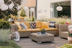Fleurs sur la table de rotin près du divan avec les coussins modelés sur la terrasse avec des lanternes images libres de droits
