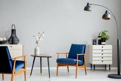 Fleurs sur la table en bois entre les fauteuils bleus dans l'intérieur plat gris avec la lampe noire photographie stock libre de droits