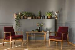 Fleurs sur la table en bois entre les fauteuils rouge foncé dans le gre simple images libres de droits