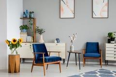 Fleurs sur la table entre les fauteuils bleus dans l'intérieur de salon avec des affiches et les tournesols Photo réelle image stock