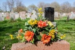 Fleurs sur une pierre tombale dans un cimetière Photographie stock