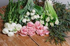Fleurs sur une vieille table en bois Espace de travail de fleuriste : homme faisant les décorations florales Photos libres de droits