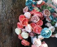 Fleurs synthétiques multicolores dehors sur la rue près d'un tronc d'arbre Image stock