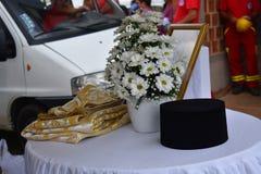 Fleurs, tissus et chapeaux des prêtres images stock