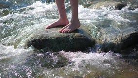 Fleuve de montagne Le type se tient sur une roche, les écoulements d'eau autour de ses pieds et la pierre Voyageur de début de la banque de vidéos