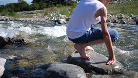 Fleuve de montagne Le type se tient sur une roche, les écoulements d'eau autour de ses pieds et la pierre Voyageur de début de la clips vidéos
