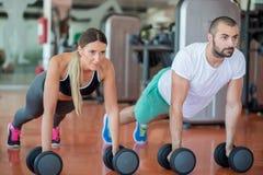 Flexão de braço da força da flexão de braço do homem e da mulher do Gym com peso em um exercício foto de stock