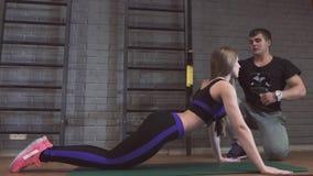 A flexão de braço da força da flexão de braço do homem e da mulher do Gym em uma aptidão malha filme