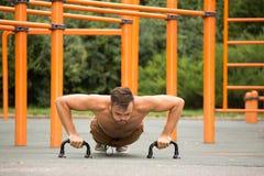 Flexões de braço do treinamento do modelo da aptidão do homem fora Fotos de Stock