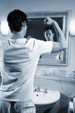 Flex one´s muscles. A young attractive man is standing in his bath and flex one ´s muscles Stock Image