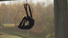 Flexibel brunette die sommige acrobatische elementen op luchthoepel in openlucht doen stock videobeelden