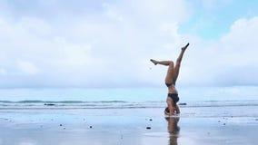 Flexibele yogavrouw die voorwaartse kromming wat betreft voorhoofd aan overzees van de knieën in openlucht zonsondergang strand u stock video