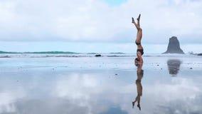 Flexibele yogavrouw die voorwaartse kromming wat betreft voorhoofd aan overzees van de knieën in openlucht zonsondergang strand u stock videobeelden