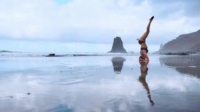 Flexibele yogavrouw die voorwaartse kromming wat betreft voorhoofd aan overzees van de knieën in openlucht zonsondergang strand u stock footage