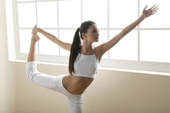 Flexibility. Young woman doing yoga or stretching, arm outstretched Stock Photos
