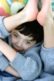 Flexibility. A boy turning both feet up to his head, showing extreme flexibility of a young child royalty free stock images