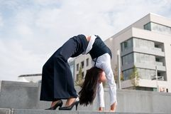 Flexibility - business woman. Outdoors making gymnastics pose, office building in background Stock Image