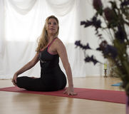 Flexibility and Grace. A yoga instructor in a studio setting seated in full lotus twisting and looking behind her to improve flexibility Royalty Free Stock Image