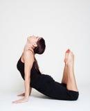 Flexibility woman doing exercises. Flexibility woman in black sportswear doing exercises Royalty Free Stock Image