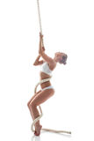 Flexible aerialist posing on rope in studio Royalty Free Stock Image