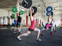 Flexible Athletes Exercising With Barbells In Gym. Flexible male and female athletes exercising with barbells in gym Stock Photography