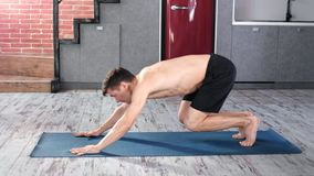 Flexible athletic Caucasian male practicing yoga exercise at home full shot. Active yogi man having slim sports body enjoying training workout on mat side view stock video footage