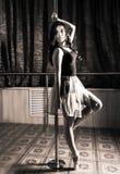 Flexible ballet dancer stretching in retro style. Ballerina dances near pole Royalty Free Stock Photos