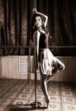 Flexible ballet dancer stretching in retro style. Ballerina dances near pole Royalty Free Stock Image