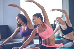 Flexible beauties. Young beautiful young women with perfect bodies in sportswear doing stretching with smile at gym Royalty Free Stock Image