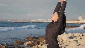 Flexible brunette girl makes side bends on the sea coast slow motion
