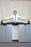 Flexible business man in the center,  split position on cabinets. Fit, flexible business man in the center, or straddle, split position on cabinets Royalty Free Stock Photo