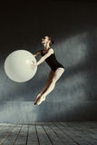 Flexible charismatic gymnast performing using the white balloon Royalty Free Stock Photos