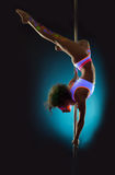 Flexible contemporary dancer exercising on pole Stock Photo