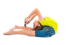 Flexible contortionist kid girl playing with tablet pc. On white background Stock Images