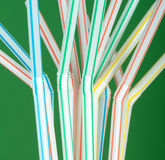 Flexible Drinking Straws. Closeup of a group of striped, disposable, flexible drinking straws on a green background Royalty Free Stock Photos