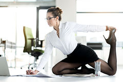 Flexible female working on table at office stock photos