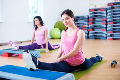 Flexible fit women stretching legs with aerobic step platforms. Flexible fit women stretching legs with aerobic step platforms Stock Photography