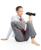 Flexible forecast. Business woman sitting in flexible pose and holding binoculars with her leg Royalty Free Stock Image