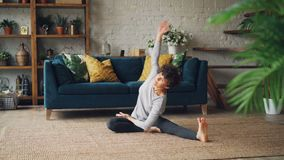 Flexible girl is bending forward in seated position and twisting her body enjoying yoga and activity sitting on floor in. Beautiful apartment. People, lifestyle stock footage