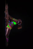Flexible girl dancing on pole under UV light Royalty Free Stock Images