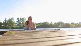 Flexible girl does stretching on small wooden pier. Flexible sporty girl does stretching on a small wooden pier on the lake. Morning work-out outdoors, sports stock video footage
