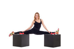 Flexible girl doing gymnastic splits on cubes. Flexible young girl doing gymnastic splits on cubes Royalty Free Stock Images